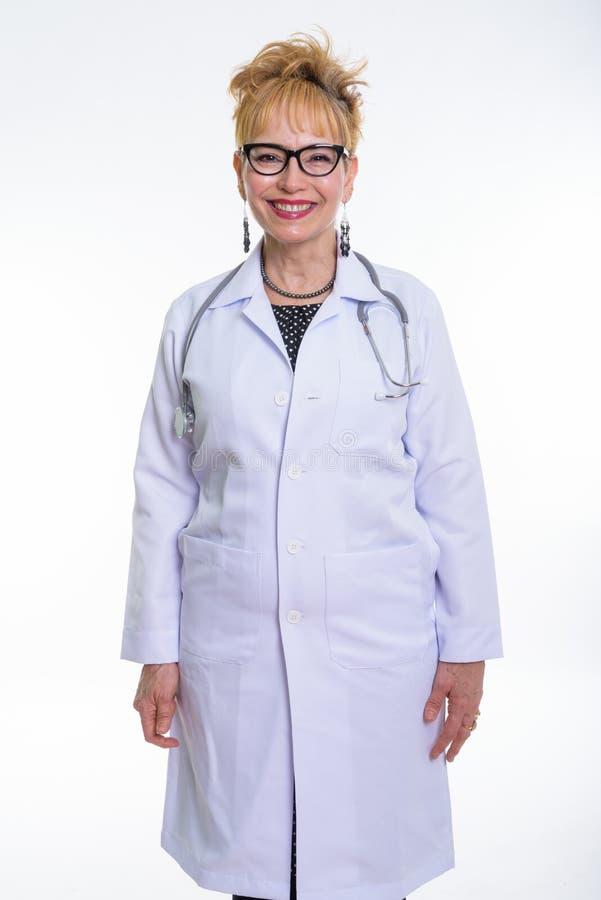 Estúdio disparado do sorriso e do suporte asiáticos superiores felizes do doutor da mulher imagem de stock royalty free