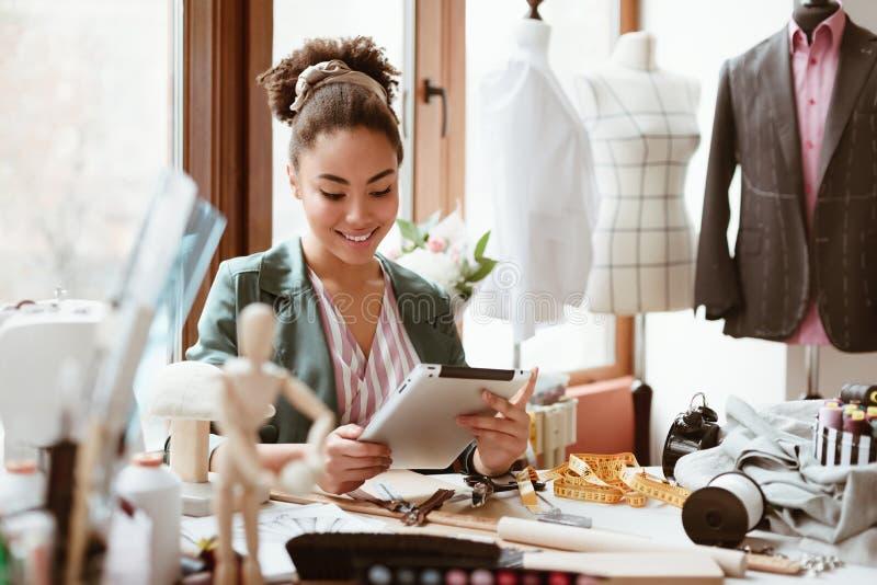 Estúdio do projeto O alfaiate da jovem mulher com tabuleta digital está modelando a roupa nova fotos de stock
