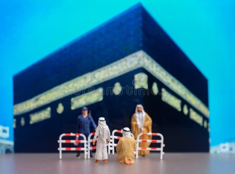 Estúdio filmado de miniatura em roupas árabes e segurança restringem peregrinos de rezar no Kaabah Devido ao código 19, Ka fotografia de stock royalty free