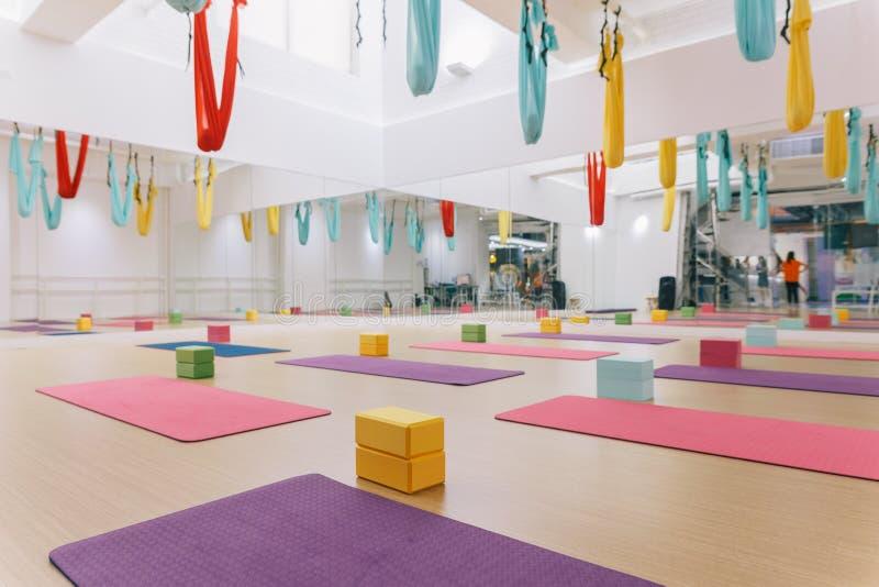 Estúdio vazio da ioga do voo com as redes coloridas com blocos coloridos da ioga e as esteiras no assoalho de madeira da textura  foto de stock