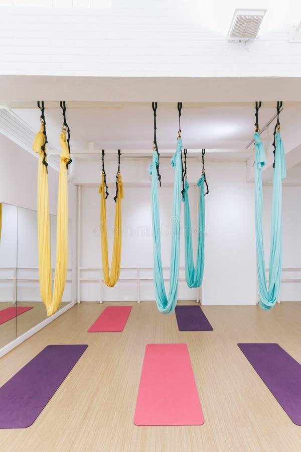 Estúdio vazio da ioga do voo com as redes coloridas com as esteiras coloridas da ioga no assoalho de madeira da textura no estúdi imagem de stock