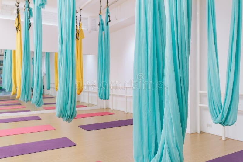 Estúdio vazio da ioga do voo com as redes coloridas com as esteiras coloridas da ioga no assoalho de madeira da textura no estúdi foto de stock royalty free