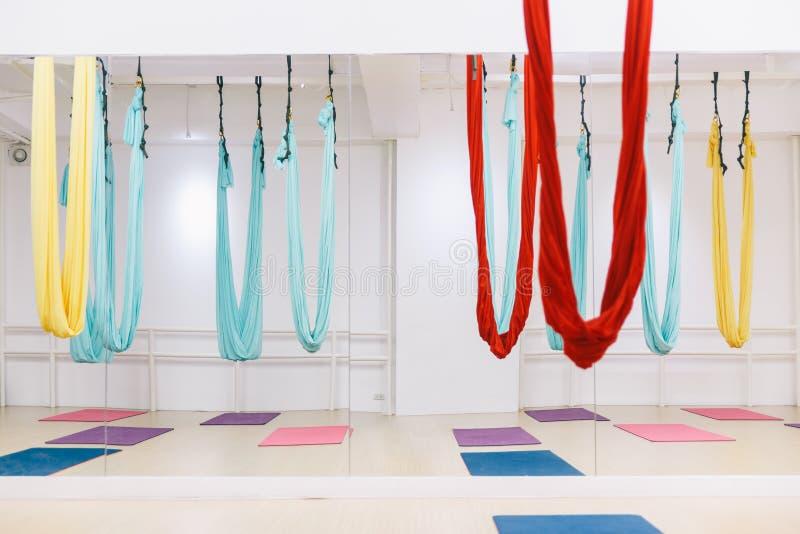 Estúdio vazio da ioga do voo com as redes coloridas com as esteiras coloridas da ioga no assoalho de madeira da textura no estúdi imagens de stock