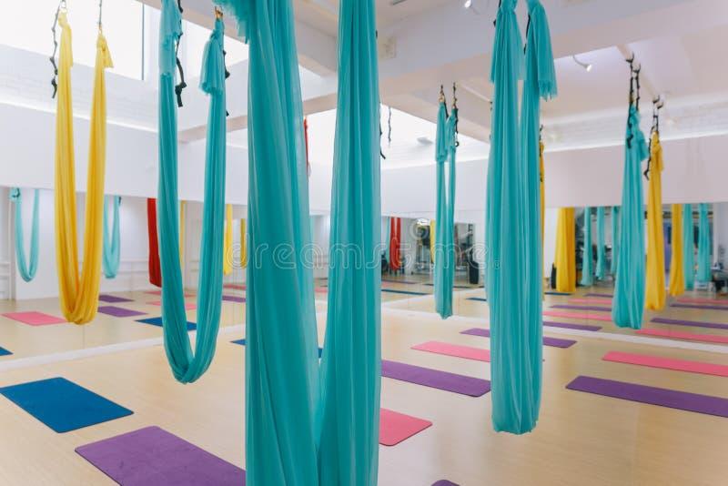 Estúdio vazio da ioga do voo com as redes coloridas com as esteiras coloridas da ioga no assoalho de madeira da textura no estúdi foto de stock