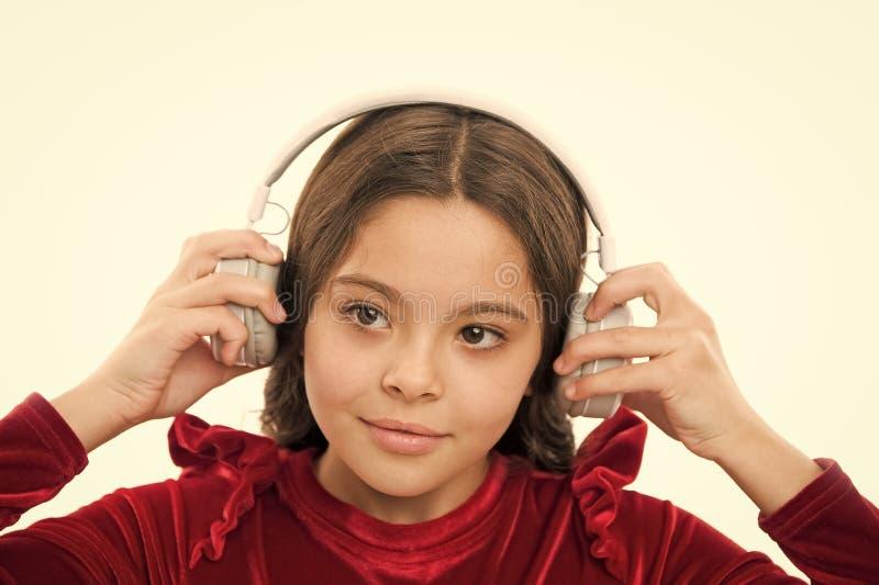Est? atentas las nuevas y pr?ximas canciones populares libres ahora La ni?a escucha los auriculares inal?mbricos de la m?sica M?s foto de archivo