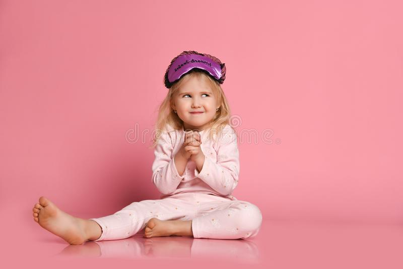 Est?dio disparado da jovem mulher bonita satisfeito que levanta no eyemask A menina bonito pequena alegre nos pijamas senta-se no foto de stock royalty free