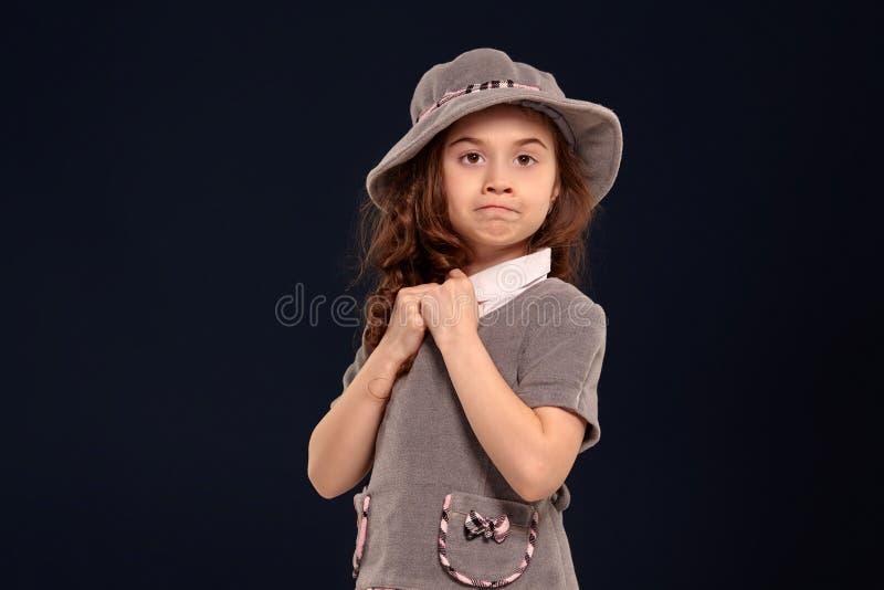 Est?dio disparado de uma crian?a bonita com um cabelo longo, encaracolado que levanta em um fundo preto imagens de stock