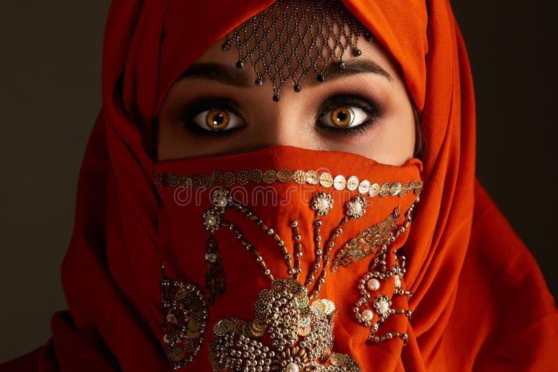 Est?dio disparado de uma mulher encantador nova que veste o hijab da terracota decorado com lantejoulas e joia Estilo ?rabe fotos de stock
