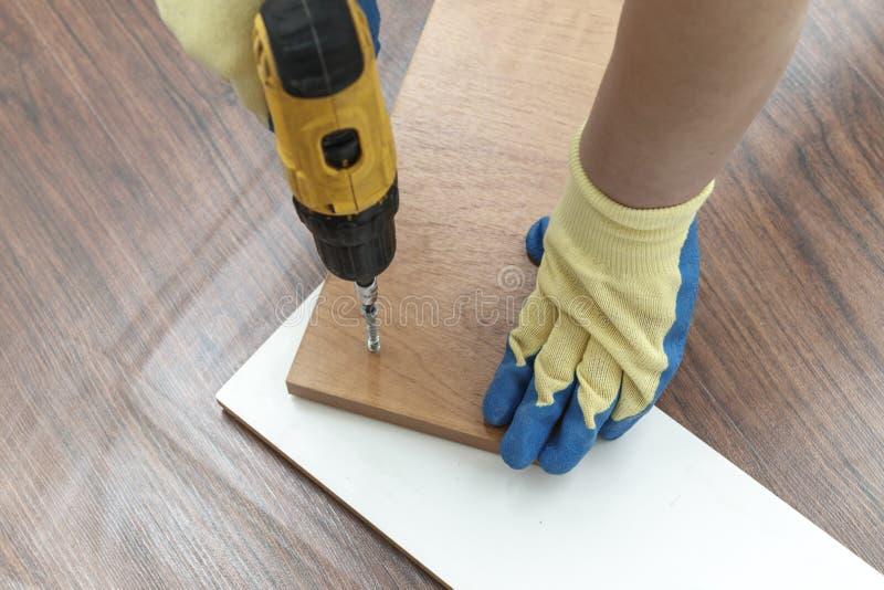 est le processus d'assembler des meubles de carton gris dans les mains d'un tournevis rechargeable pour serrer des vis photo stock