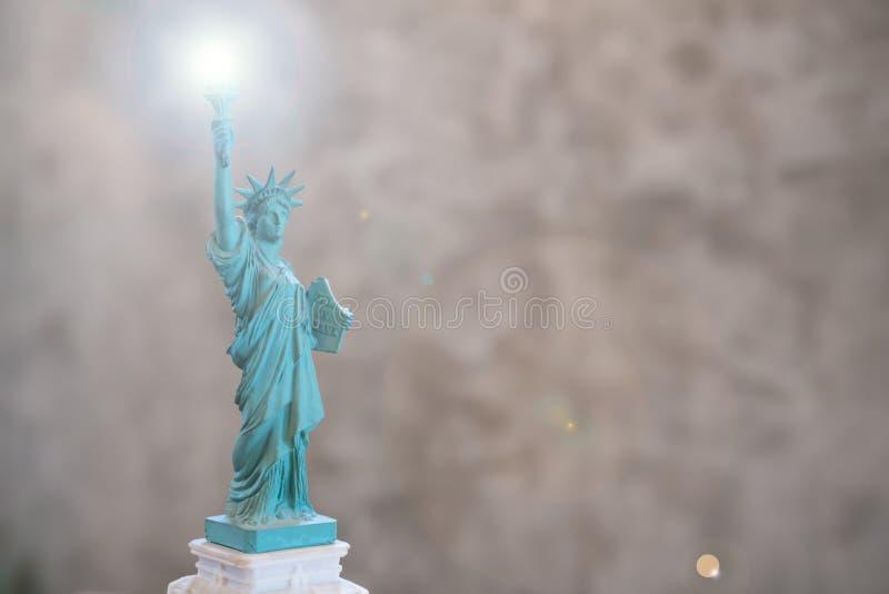 A est?tua da liberdade COM len o efeito do alargamento na tocha no assistente no fundo de lustro concreto da parede fotos de stock royalty free