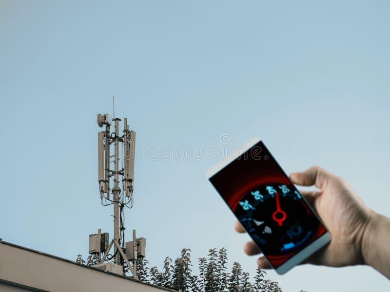 Estação base do telefone celular no telhado e no velocímetro móvel da rede na tela do telefone fotografia de stock