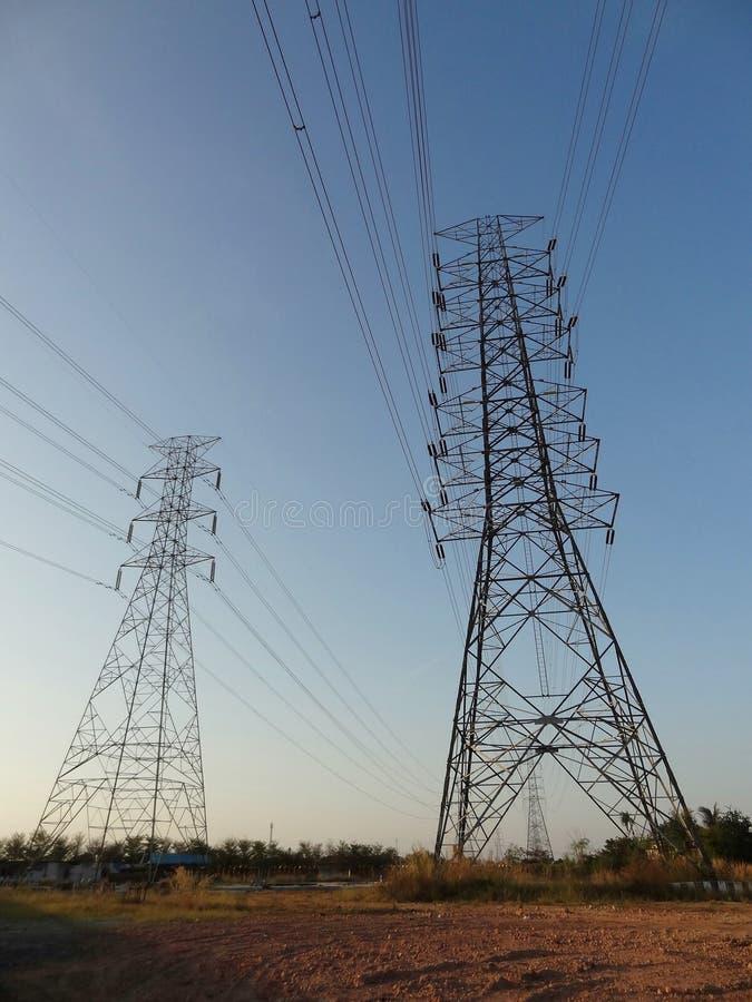 Estação de alta tensão da torre do pilão do polo da eletricidade contra o céu azul imagem de stock