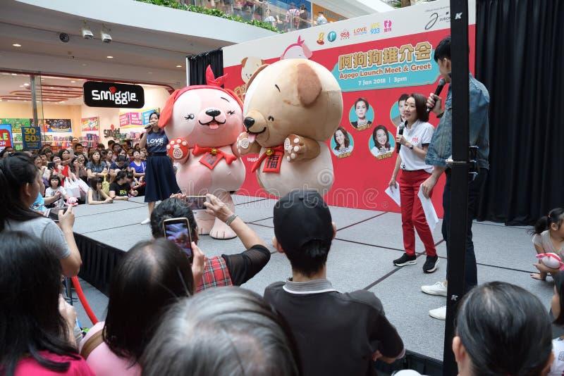 Estação de rádio chinesa DJs de Singapura Mediacorp e ano das mascote do cão fotografia de stock royalty free