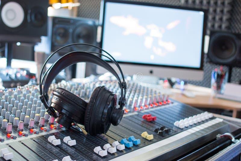Estação de rádio: Fones de ouvido em uma mesa do misturador em um estúdio de gravação sonora profissional foto de stock