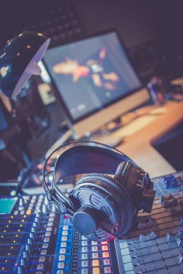 Estação de rádio: Fones de ouvido em uma mesa do misturador em um estúdio de gravação sonora profissional fotos de stock