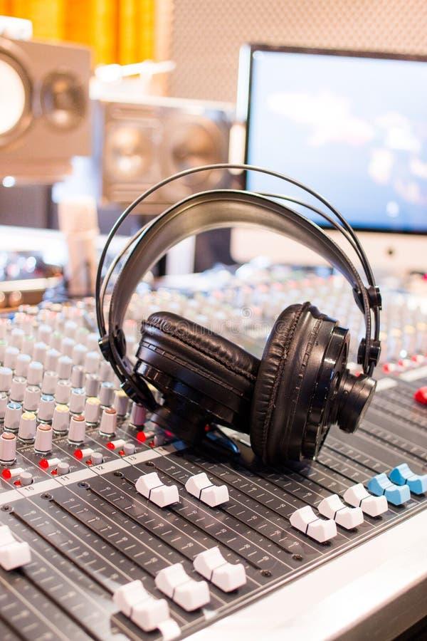 Estação de rádio: Fones de ouvido em uma mesa do misturador em um estúdio de gravação sonora profissional imagens de stock