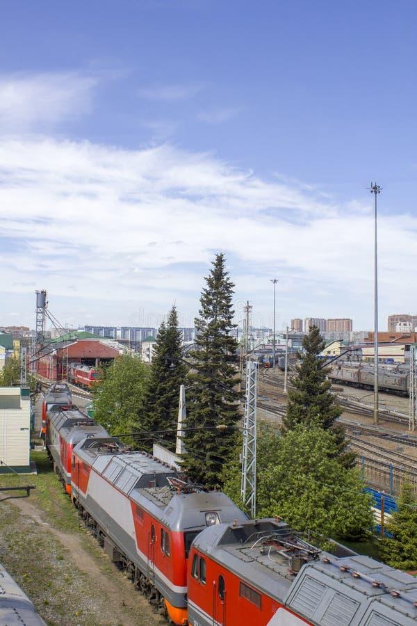 Estação de trem com muitos caminhos de ferro e a composição do trem com os carros no fundo da cidade, vista aérea foto de stock