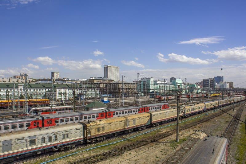Estação de trem com muitos trens multi-coloridos com os carros no fundo de construções modernas da cidade, vista aérea foto de stock
