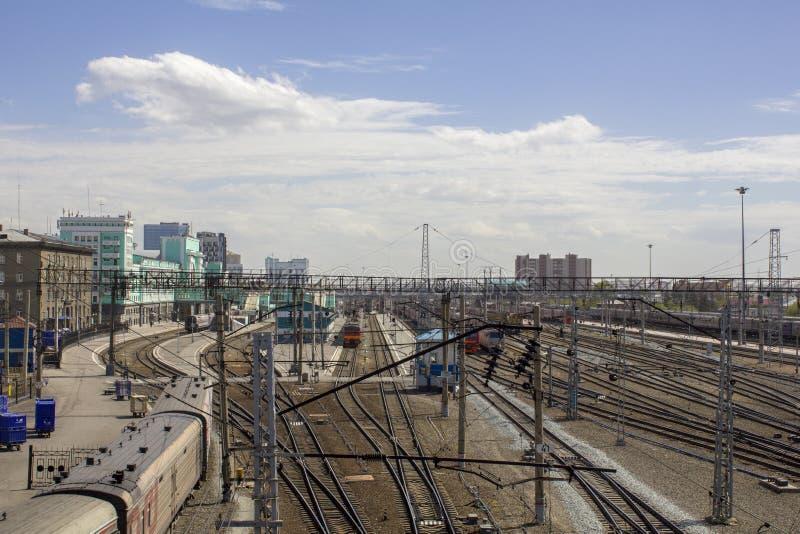 Estação de trem com muitos trilhas de estrada de ferro e trens modernos no fundo de construções da cidade imagem de stock