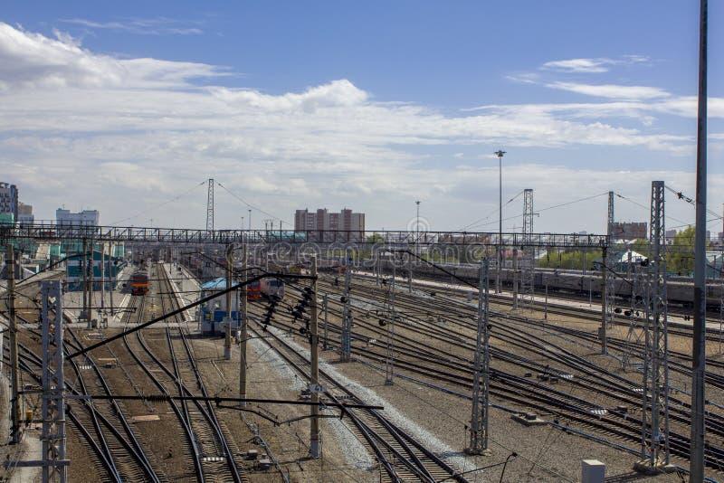 Estação de trem com muitos trilhas de estrada de ferro e trens modernos no fundo das construções da cidade sob um céu azul foto de stock royalty free