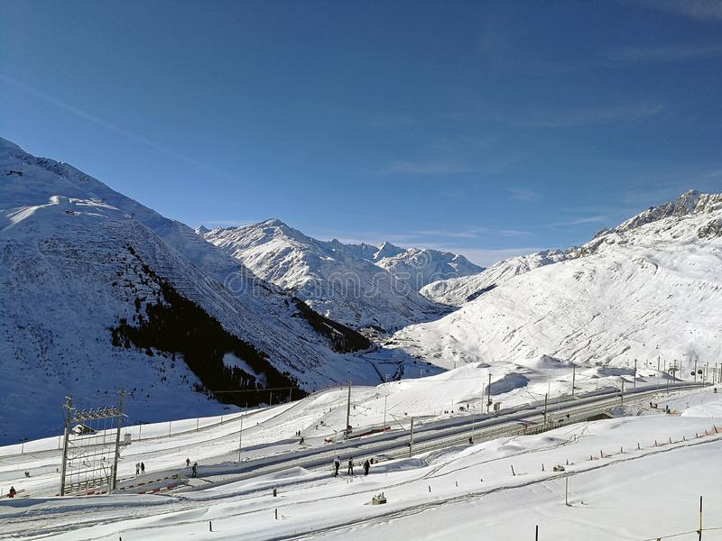 Estação de trem suíça entre montes cobertos de neve na luz do sol bonita imagem de stock royalty free