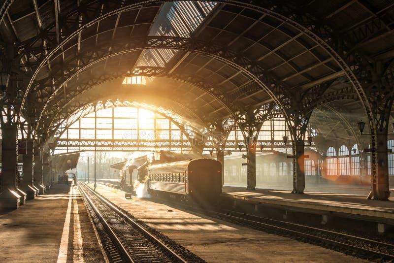 Estação de trem velha com um trem e uma locomotiva na plataforma que espera a partida Nivelando raios da luz do sol em arcos do f imagens de stock