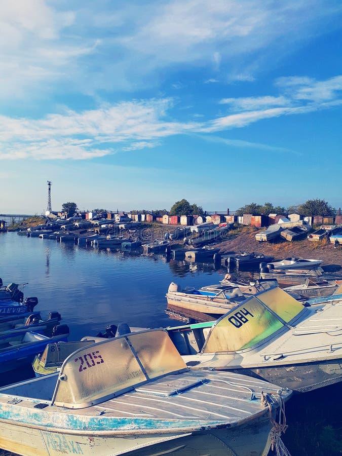 Estação do barco no alvorecer de um dia ensolarado do verão com lotes dos barcos e um céu azul que reflete na água imagens de stock royalty free