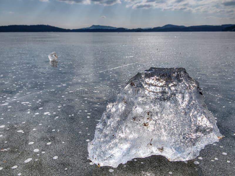 Estação do inverno no rio congelado Sincelos de brilho quebrados no nível de água leitoso congelado fotos de stock