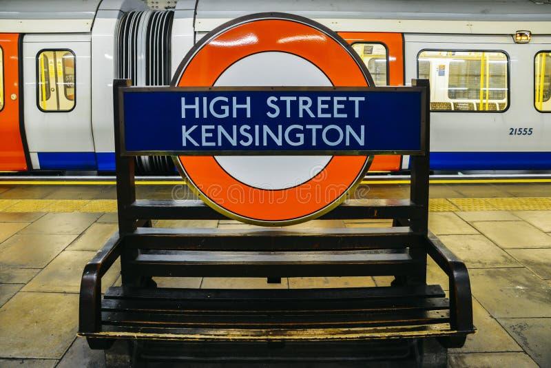 A estação subterrânea de Kensington da rua principal que mostra o tubo icônico assina dentro a plataforma das linhas do distrito  fotos de stock