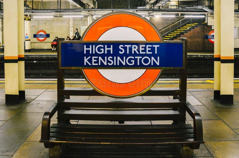 A estação subterrânea de Kensington da rua principal que mostra o tubo icônico assina dentro a plataforma das linhas do distrito  imagem de stock