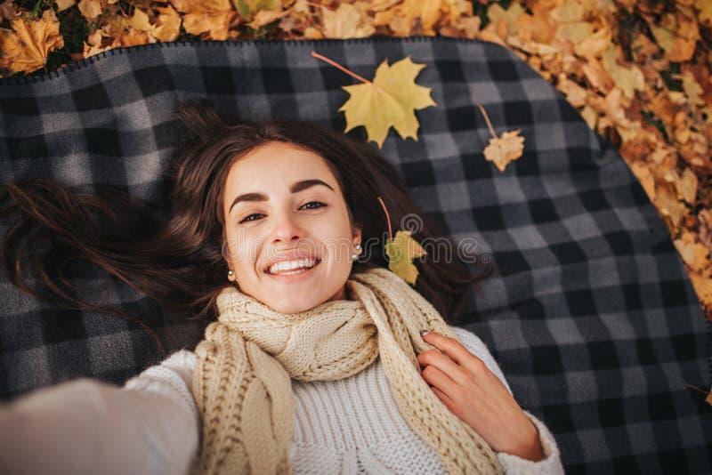 Estação, tecnologia e conceito dos povos - jovem mulher bonita que encontra-se na terra e nas folhas de outono e que toma o selfi imagens de stock
