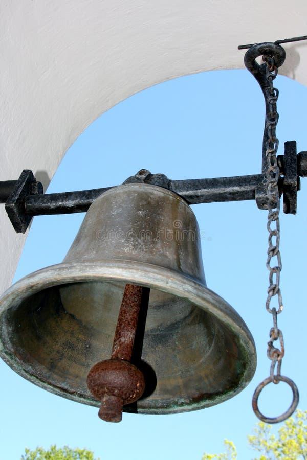 Estaño y campana de cena negra en el arco blanco con el cielo azul foto de archivo
