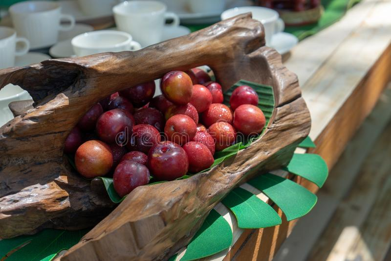 Esta é ameixa vermelha de Tailândia é ácido e adstringente está na cesta de madeira da arte no contador de madeira fotografia de stock royalty free