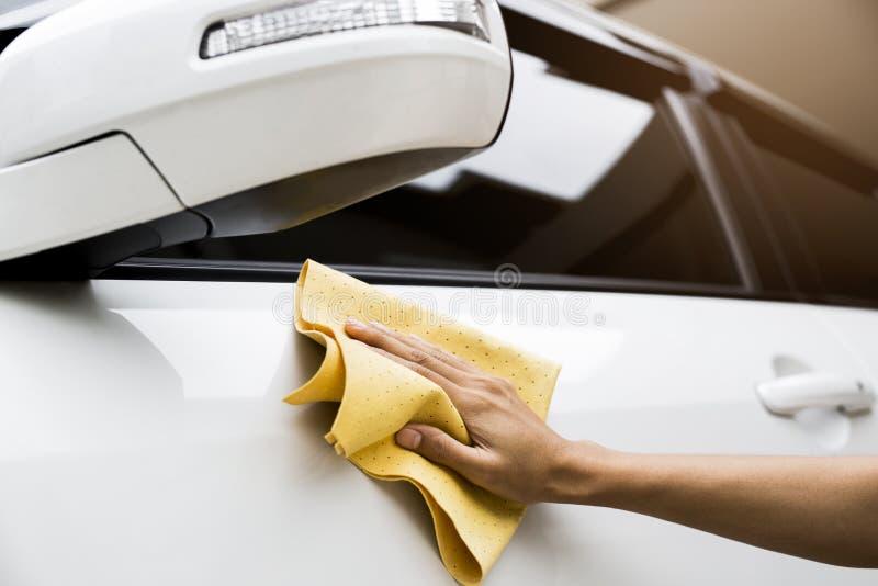 Esta imagem é uma imagem de limpar o carro com um pano amarelo do microfiber à mão foto de stock