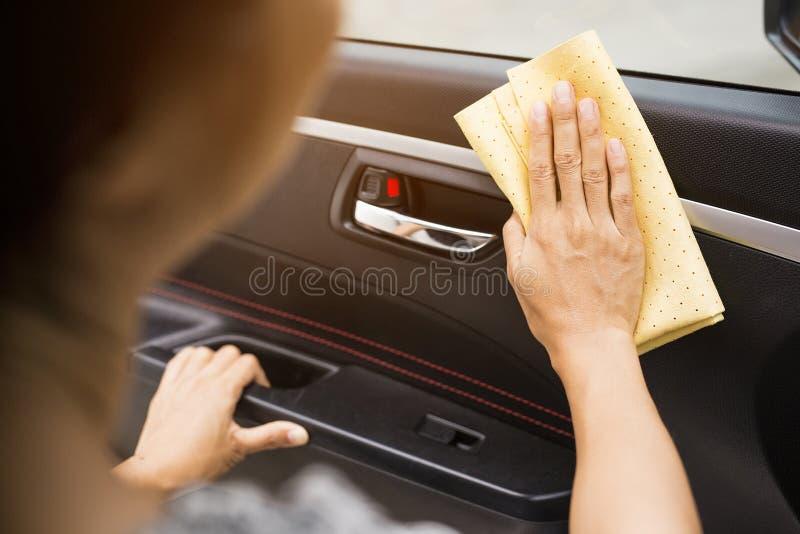 Esta imagem é uma imagem de limpar o carro com um pano amarelo do microfiber à mão fotografia de stock