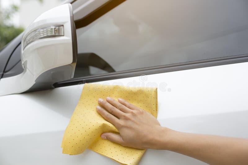 Esta imagem é uma imagem de limpar o carro com um pano amarelo do microfiber pelas mãos imagens de stock royalty free