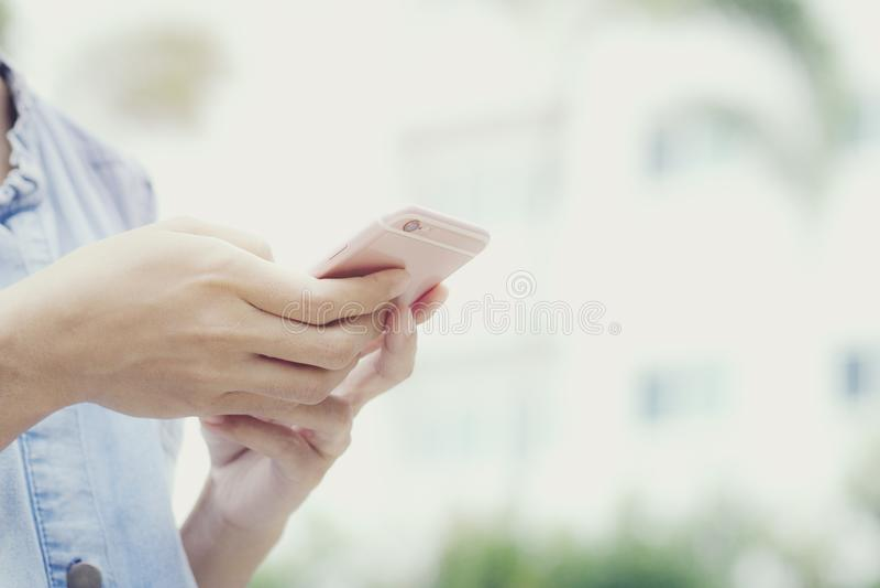 Esta imagem é uma imagem de uma mulher que usa um telefone celular com uma casa no fundo fotografia de stock royalty free