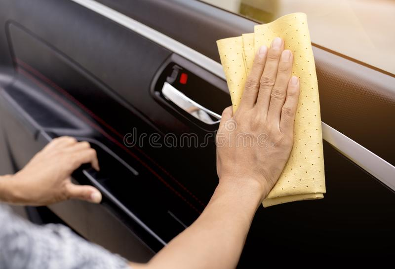 Esta imagen es una imagen de limpiar el coche con un paño amarillo de la microfibra al lado de las manos foto de archivo libre de regalías