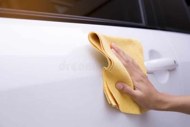 Esta imagen es una imagen de limpiar el coche con un paño amarillo de la microfibra al lado de las manos imagen de archivo libre de regalías