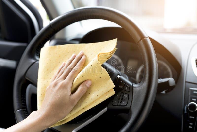 Esta imagen es una imagen de una mano que limpia el volante con un paño de la microfibra fotos de archivo libres de regalías