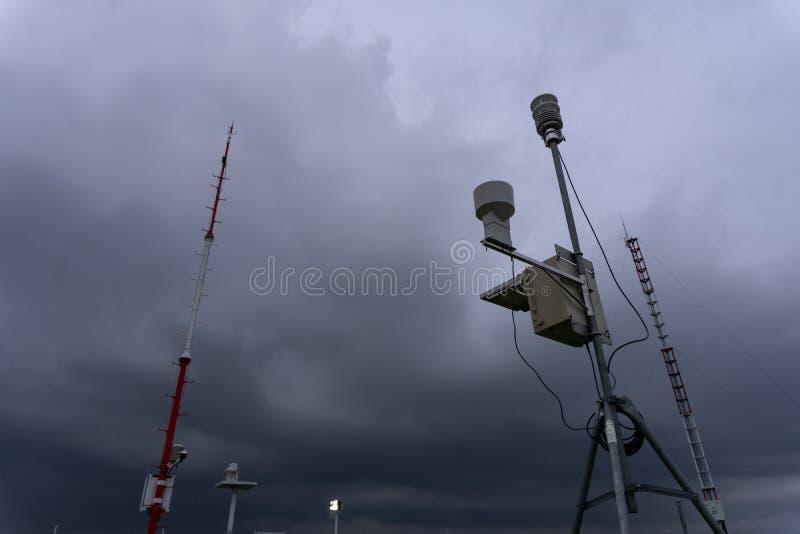 Esta??o meteorol?gica autom?tica port?til no aeroporto de Ngurah Rai sob as nuvens de c?mulo-nimbo escuras assustadores Esta ferr fotografia de stock royalty free