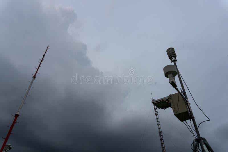 Esta??o meteorol?gica autom?tica port?til no aeroporto de Ngurah Rai sob as nuvens de c?mulo-nimbo escuras assustadores Esta ferr imagem de stock