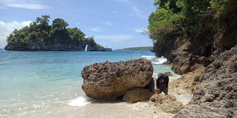 Esta praia de pedra de Canggu, o viajante não somente pode testemunhar a existência de um templo original igualmente tem uma área fotografia de stock