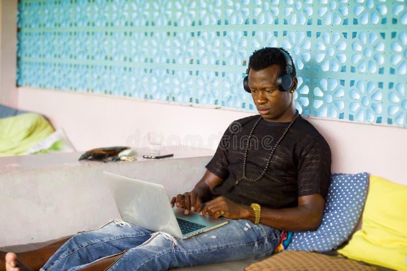 Establecimiento de una red afroamericano atractivo y del inconformista del negro de negocios del hombre con el ordenador port?til foto de archivo