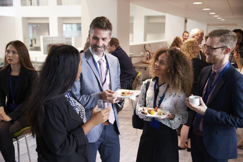 Establecimiento de una red de los delegados durante hora de la almuerzo de la conferencia fotografía de archivo libre de regalías
