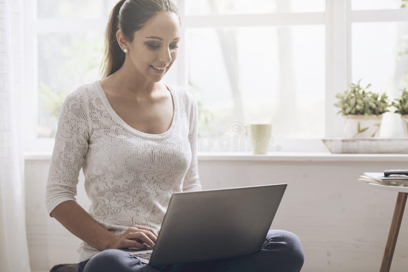 Establecimiento de una red de la mujer joven con su ordenador portátil en casa fotografía de archivo