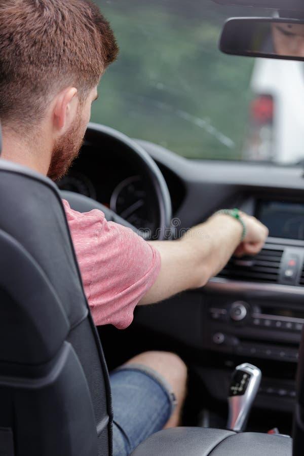 Estación de radio cambiante del hombre mientras que conduce el coche imagen de archivo