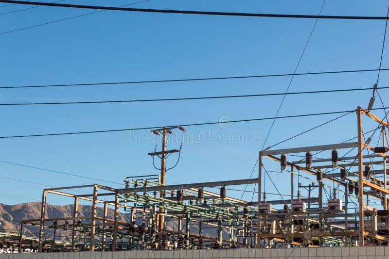 Estación de transferencia de la corriente eléctrica contra la cordillera, cielo azul fotografía de archivo libre de regalías