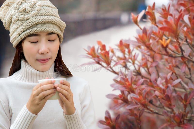 Estación del invierno y del otoño La mano del ` s de la mujer que sostiene una taza blanca de café caliente en día acogedor, se r imagenes de archivo