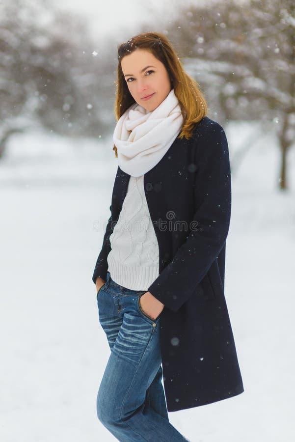 Estación, la Navidad, días de fiesta y concepto de la gente - la mujer joven sonriente en invierno viste al aire libre foto de archivo libre de regalías